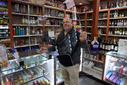 Magnum Tools owner Dan Martin displays a sneeze guard that can be used in retail stores  at a Sunoco station in Southgate on Friday, March 27, 2020.