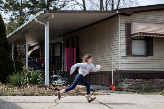 Isabella Patterson, 10, runs across the driveway to show off her cheerleading skills outside of her home in Clinton Township, Friday, March 27, 2020.