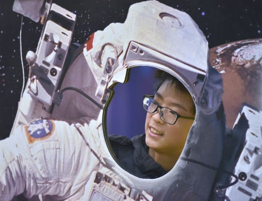 Nicholas Chang, 11, of Windsor, Ontario, Canada, poses looking through an astronaut cutout at the Michigan Science Center in April 2019.