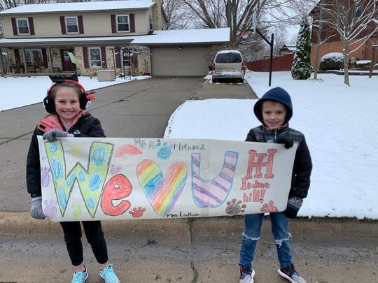 Annabelle Schaub and Paxton  Schaub of Grand Blanc hold up a sign during Indian Hill Elementary School's social distancing parade on March 23.