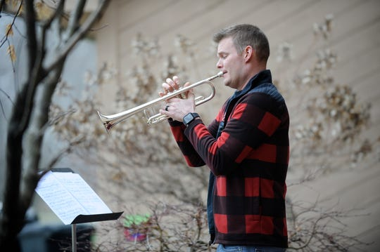 Hunter Eberly, principal trumpet for the Detroit Symphony Orchestra, plays a song from the movie Godfather on the front steps of his Grosse Ile home, Thursday, March 26, 2020. Mr. Eberly and other members of the DSO have been playing from their homes at 6 p.m. to bring a bit of joy to their neighborhoods during the coronavirus pandemic.