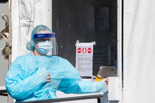 A member of the Brooklyn Hospital Center testing team enters their COVID-19 testing site, Thursday, March 26, 2020, in New York.