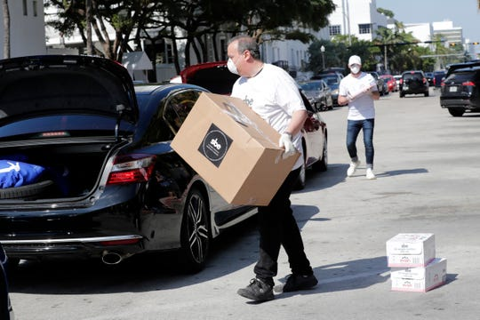 An employee of the sbe hotel chain loads a box of supplies into the vehicle of an sbe hotel employee outside of the SLS Hotel, Thursday, March 26, 2020, in Miami Beach, Fla.