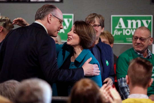 FILE - In this Feb. 1, 2020 file photo Democratic presidential candidate Sen. Amy Klobuchar, D-Minn., center, gets a kiss from husband John Bessler, upon arriving at a rally in Sioux City, Iowa.