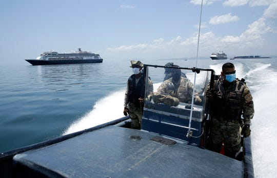 Panamanian Navy Police navigate near the anchored Zaandam cruise ship, carrying some guests with flu-like symptoms, after it arrived to the bay of Panama City, Friday, March 27, 2020.