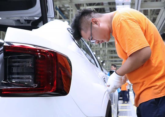 A worker assembles a Polestar 2 EV in Luqiao, China. Volvo has begun production of the all-new car which will be exported to Europe and the U.S. It is key to the automaker's electrification plans.