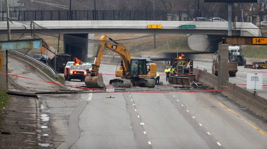 Workers clean debris from a collapsed pedestrian bridge on westbound Interstate 94 near Van Dyke Avenue Friday, March 27, 2020 in Detroit.