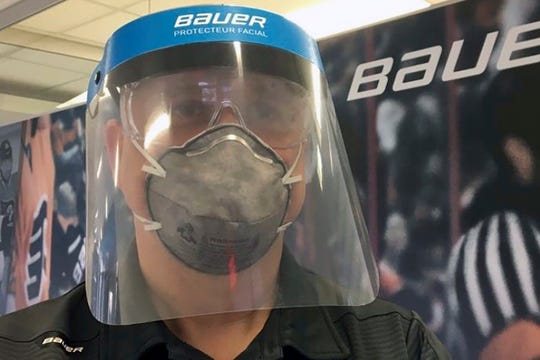 In this March 23, 2020, photo provided by Bauer Hockey Corp., an employee models a medical face shield the hockey equipment manufacturer has begun creating to help those treating the coronavirus pandemic, at Bauer Hockey Corp. in Blainville, Quebec.