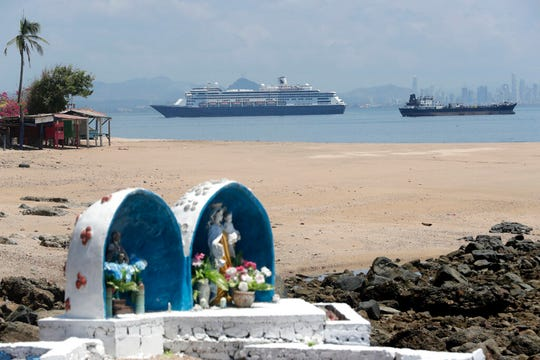 The Zaandam cruise ship, top center, carrying dozens of guests with flu-like symptoms, arrives to the bay of Panama City, seen from Isla de Taboga, Panama, Friday, March 27, 2020, amid the worldwide spread of the new coronavirus.