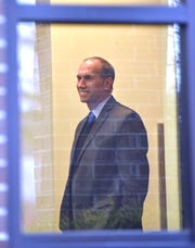 Macomb County Prosecutor Eric Smith stands in the lobby as he prepares to be fingerprinted.