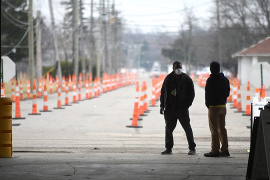 Workers wait for vehicles to arrive for testing in the motor vehicle lanes on the first day of testing at the new regional COVID-19 testing facility at the former Michigan State Fairgrounds site in Detroit on Friday, March 27, 2020.