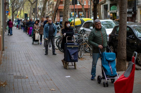 People line up to buy supplies from a shop during the coronavirus outbreak in Barcelona, Spain, Friday, March 27, 2020.