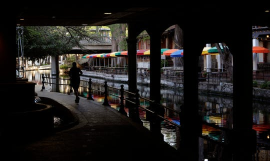 In this March 24, 2020, file photo, a runner moves along a mostly deserted River Walk in San Antonio, where most restaurants and business are closed.