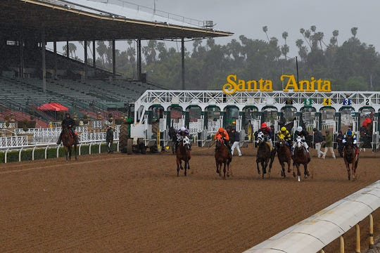 Horses run in the fourth race at Santa Anita Park in front of empty stands March 14 in Arcadia, Calif.