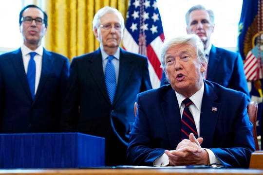 President Donald Trump speaks before signing the coronavirus stimulus relief package, at the White House, Friday, March 27, 2020, in Washington, as from left, Treasury Secretary Steven Mnuchin, Senate Majority Leader Mitch McConnell of Ky., and House Minority Kevin McCarthy of Calif., look on.
