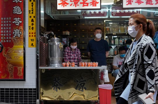 People wear their face masks on the streets of Hong Kong Thursday, March 26, 2020.