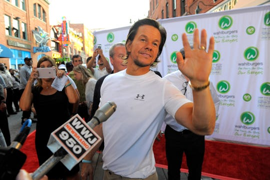 Mark Wahlberg, waves to the crowd, Aug. 10, 2016, outside the Wahlburgers in Detroit's Greektown.