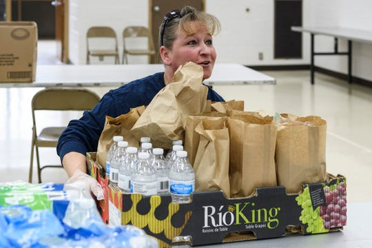 Volunteer Kristi White prepares to carry a large load of grab-and-go meals to the front of Evansville's CK Newsome Community Center to hand out to anyone who needs lunch, Thursday afternoon, March 26, 2020. The Feed Evansville Unofficial Task Force is collecting donations for the food program Monday-Friday at the community center.
