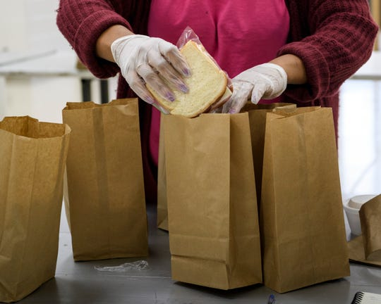 Volunteer Tyhetia Stuart packs sandwiches into grab-and-go food bags at the CK Newsome Community Center in Evansville, Ind., Thursday, March 26, 2020. The Feed Evansville Unofficial Task Force is offering grab-and-go and neighborhood delivery meals to those in need due to economic hardships faced by the COVID-19 pandemic.