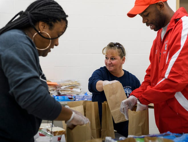 Tanisha Carothers, from left, Kristi White and City Councilman Alex Burton fill grab-and-go food bags to give out in front of CK Newsome Community Center in Evansville, Ind., Thursday afternoon, March 26, 2020. The Feed Evansville Unofficial Task Force is collecting donations for the food program Monday-Friday at the community center.