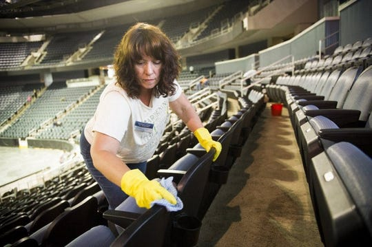 Jessica Kimmel, of French Lick, Ind., cleans seats at the Ford Center while preparing for the upcoming Jehovah's Witness summer convention, Thursday, June 9, 2016. Thousands of Jehovah's Witnesses attend the convention over two weekends, but the coronavirus pandemic's shelter-in-place order has put the hotel industry in dire economic straights.