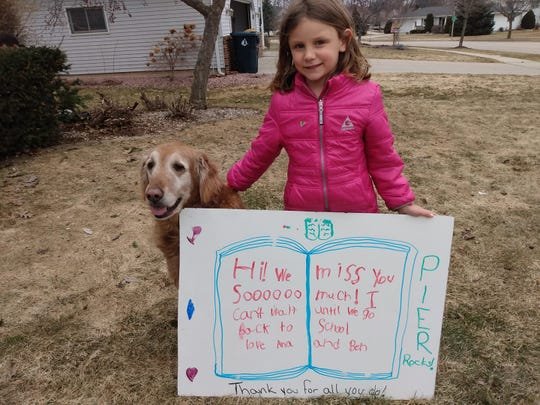 """Pier Elementary School student  Ana Neumann stands with a sign she made to say """"hi"""" to school staff during their car parade on Tuesday, March 24, 2020."""