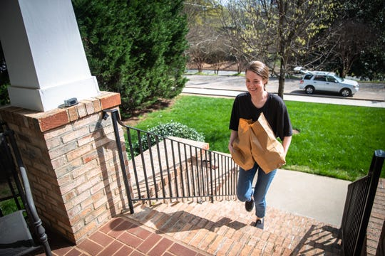 Hallie Weems, a third-year medical student at University of South Carolina School of Medicine Greenville, delivers groceries to George Hammond, 77 and Jan Amacher, 71, Friday, March 27, 2020.