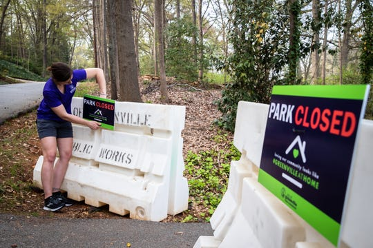Marlie Creasey-Smith, the Director of Parks and Rec with the city of Greenville, attaches a sign to a barricade at an entrance to Cleveland Park in Greenville, informing visitors of its temporary closure, Friday, March 27, 2020.
