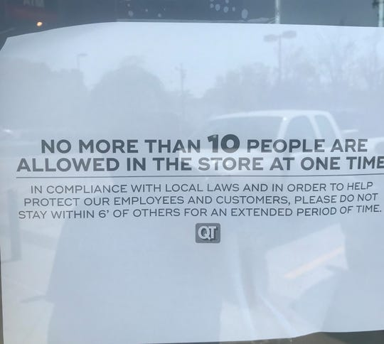 A notice about a limit on customers is posted on the door of the QuikTrip on North Main Street in Anderson.