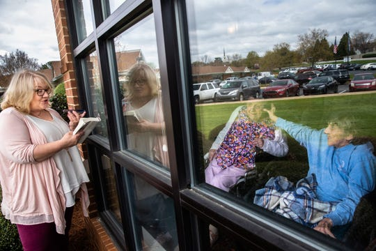 Liz Cone reads a book to Jerrie Brown, 81, and Jackie Wallace, 96, outside a window at NHC HealthCare center in Greenville, Thursday, March 26, 2020. NHC is one of many senior living facilities which have allowed family members to visit their loved ones from outside a window as a result of the coronavirus outbreak.