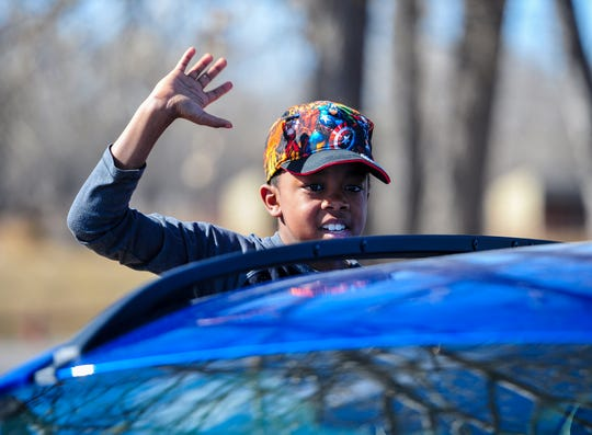 Kaeden Reid, a fifth grader at Mountain View Elementary School, waves to Mountain View teachers as they parade through their district on Thursday afternoon.