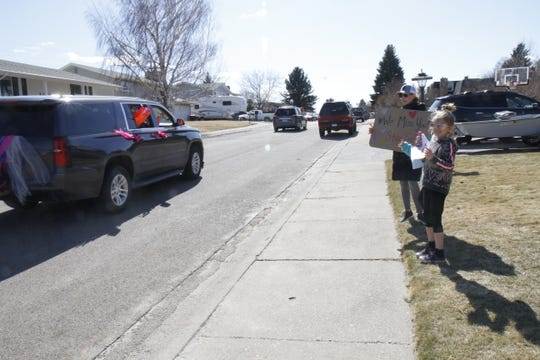 Sandra Boedecker and her daughters Macy and Sadie wave at Mountain View Elementary School staff as they drive the route for the teacher parade on Thursday, Mar. 26, 2020.