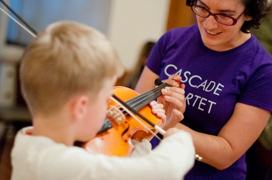 Cascade Quartet violinist Megan Karls helps a boy position his fingers on the strings during a Chamber Fun 101 event in September 2019.