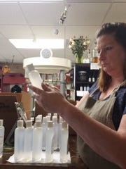 Tammy Galyon adds a label with ingredient list as the last step in her production of organic hand sanitizer.