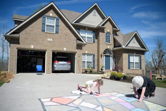 Avery Nipper, 6, and her brother Wesley, 12, draw with chalk in front of their Hardin Valley home in Knoxville, Tennessee on Thursday, March 26, 2020. Neighborhood kids have taken to drawing pictures and messages with chalk on their driveways to stay busy and creative during the coronavirus pandemic which closed most area schools.