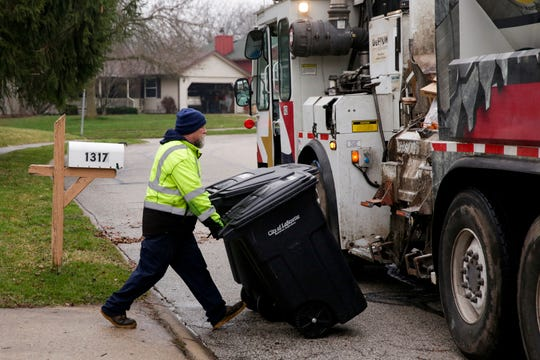 Mike Chumley, a Lafayette Streets & Sanitation worker, loads trash cans onto his truck, Friday, March 27, 2020 in Lafayette.