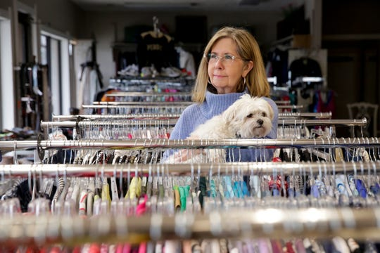 Sue Parkinson, owner of Twice As Nice Ladies Consignment Boutique, holds her dog, Maggie, as she stands in the empty Earl Avenue shop, Friday, March 27, 2020 in Lafayette.