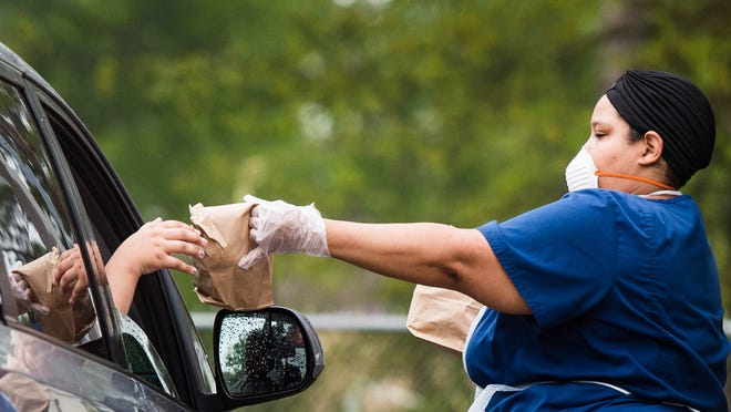 Gayelyn Thibeaux serving meals to students in make shift drive thru at Cpl. Michael Middlebrook Elementary in Lafayette, LA. Tuesday, March 17, 2020.