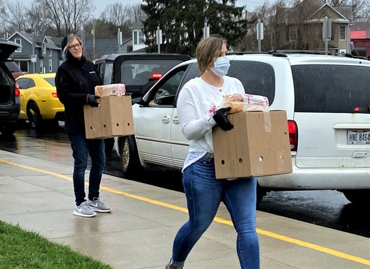 Nikki Williamson, right, carries a box of food to a family as Kristi Seymour waits for the next family at Mount Pleasant Elementary March 27. She was with a group of volunteers distributing food gathered and packed by Connexion West to help feed families during Lancaster City Schools' spring break and during the coronavirus pandemic.
