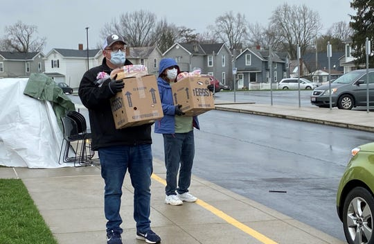Joel Seymour, right, and Cathy Tucker wait for cars to pull forward to collect boxes of food at Mount Pleasant Elementary School March 27. Seymour and Tucker were among a group of volunteers distributing food gathered and packed by Connexion West to help feed families during Lancaster City Schools' spring break and during the coronavirus pandemic.