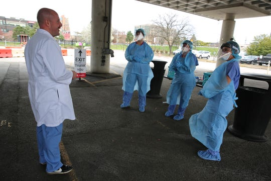 Dr. Hugh Shoff, an emergency medicine doctor, instructs health care workers at a University of Louisville Health drive-thru Covid-19 testing site.