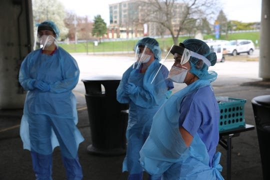 Three health care in blue protective gowns, masks and plastic eye shields at a University of Louisville Health drive-thru Covid-19 testing site.
