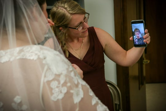 Becky Brown chats with her mom via video at Eastminster Presbyterian Church in East Lansing before her wedding ceremony March 23. She and groom Mike Brown decided to marry that evening after Michigan's 'stay home, stay safe' order was issued in the morning, foregoing a planned ceremony with 120-guests that had been planned for March 28.  Her parents dressed up but watched via social media.