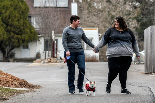 Emily Gesell, left, and her girlfriend Katie Zicarelli walk their dog Lilly after working from home on Thursday, March 26, 2020, in Lansing. For many couples, joint isolation is the new relationship milestone.