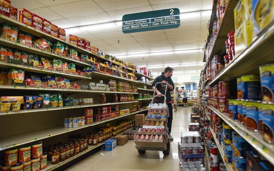 Gorman's Food Market Grocery Manager Matt Gorman replaces inventory Friday morning, March 27, 2020. Grocery stores have remained open under Gov. Gretchen Whitmer's stay-at-home order that began Tuesday. Gorman and fellow employees are considered part of the essential workforce.