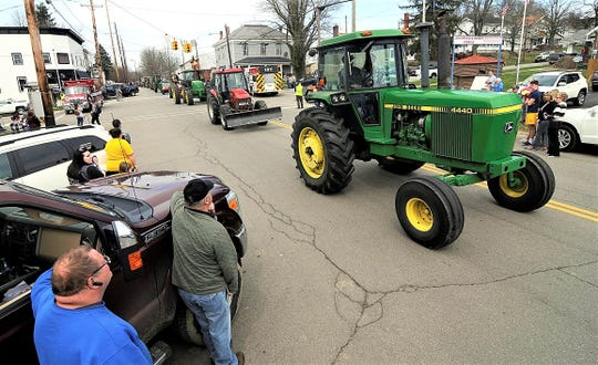 Spectators watch the funeral procession for Bill Cameron in Jeromesville, Ohio, on Thursday. Local farmers showed up with their tractors for the funeral procession after the family's private services due to the coronavirus outbreak and over 50 tractors took part in the procession.