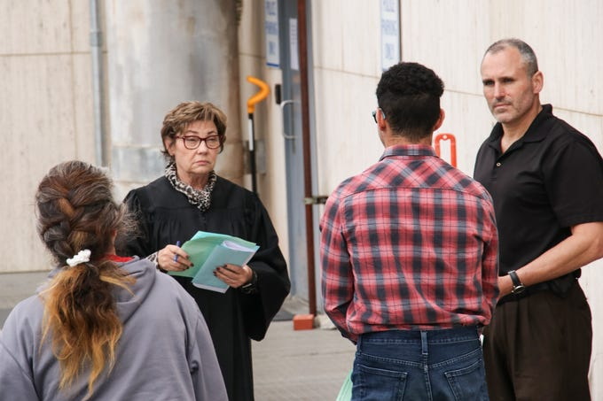 Judge Teresa Ballinger, center left, holds court outside Marion City Hall on Tuesday, March 24, after she closed the Marion Municipal Court to the public to prevent the coronavirus from spreading. Most hearings have been postponed or are being held virtually, though some defendants must be arraigned in person, outside the back doors of City Hall.