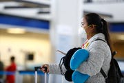 A traveler wears a protective mask as they check in at for a flight at the Memphis International Airport on Friday, March 27, 2020.