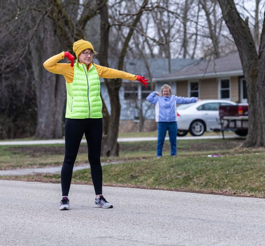 Menomonee Falls resident Nancy Siemering, right, follows along as her neighbor Maureen Lewis leads an outdoor morning exercise routine on Friday, March 27, 2020. Maureen stands in the street so participants can see her from their driveways while observing social distancing. The workout includes light stretches and exercises for 10 to 15 minutes.