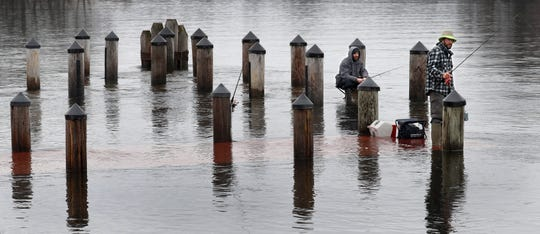 Ryan Kohlmann, left, and Jason Laven, both of Waupaca practice social distancing while fishing for walleye on a dock flooded over by the Wolf River Thursday, March 26, 2020, in Fremont, Wis. 
